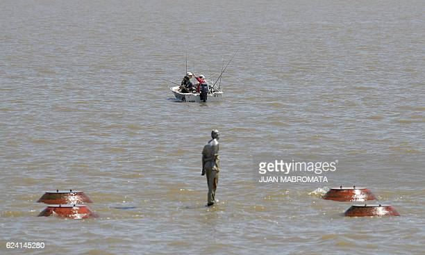 Men fish from a motorboat in the River Plate in Buenos Aires on November 18 2016 just in front of the 'Parque de la Memoria' in honour of the victims...