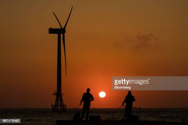 Men fishing are silhouetted in front of a wind turbine as the sun sets in the background in Jeju South Korea on Wednesday June 14 2017 The election...