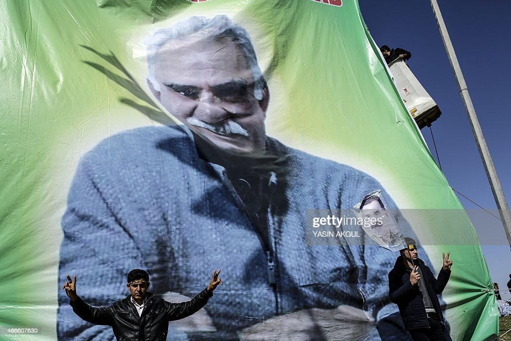 Men flash the 'V for Victory' sign near banner bearing a portrait of jailed Kurdish leader Abdullah Ocalan as they celebrate Newroz, which marks the arrival of spring and the new year, in the Turkish town of Suruc, across the border from the Syrian town of Kobani, on March 17, 2015.