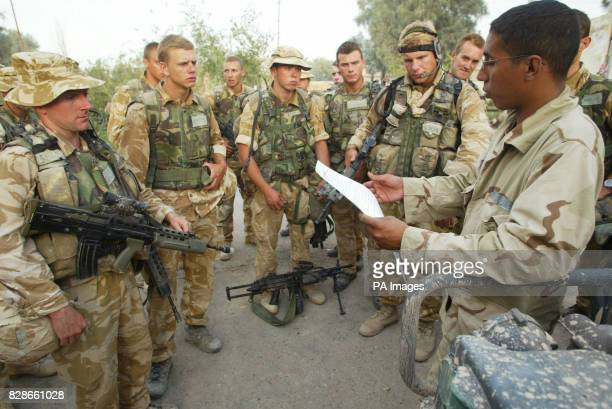 Men from Alpha company 40 Commando Royal Marines are briefed by an American interpreter before they go into the town of Abu Khasib to distribute...