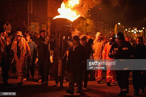 Men from the Clavie Crew carry a burning barrel on the top of a pole packed with tar soaked sticks on January 11 013 in Burghead Scotland The burning...