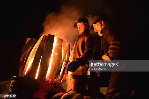 Men from the Clavie Crew carry a burning barrel packed with tar soaked sticks on January 11 013 in Burghead Scotland The burning of the Clavie takes...
