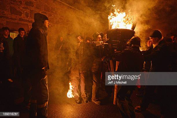 Men from the Clavie Crew carry a burning barrel packed with tar soaked sticks on the top of a pole on January 11 013 in Burghead Scotland The burning...
