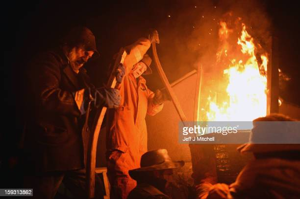 Men from the Clavie Crew stoke a burning barrel packed with tar soaked sticks on January 11 013 in Burghead Scotland The burning of the Clavie takes...