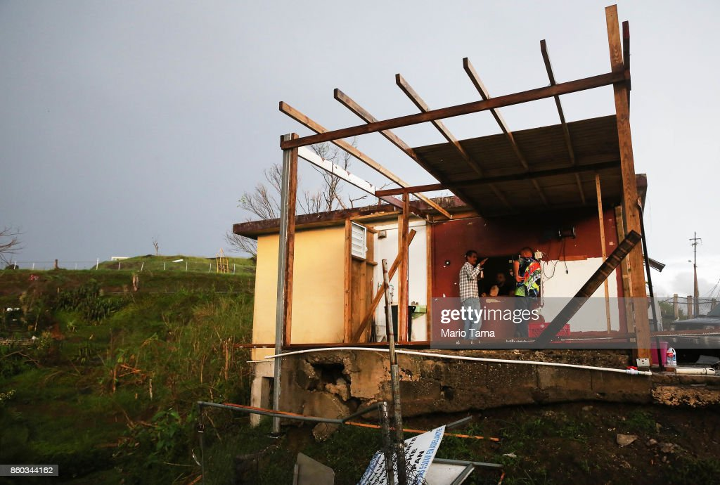 Men gather at a partially destroyed bar three weeks after Hurricane Maria hit the island, on October 11, 2017 in Aibonito, Puerto Rico. The area is without running water or grid power as a nightly curfew remains in effect. Despite multiple visits from FEMA, the town has yet to receive any FEMA aid. Only 10.6 percent of Puerto Rico's grid electricity has been restored. Puerto Rico experienced widespread damage including most of the electrical, gas and water grid as well as agriculture after Hurricane Maria, a category 4 hurricane, swept through.