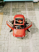 Men getting out of red car, overhead view (digital composite)