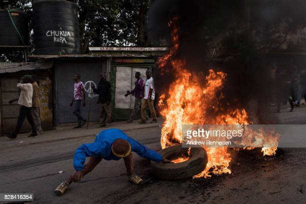 Men grabs a burning tire during a protest in Kibera Kenya's biggest slum on August 9 2017 in Nairobi Kenya The protest started after police allegedly...
