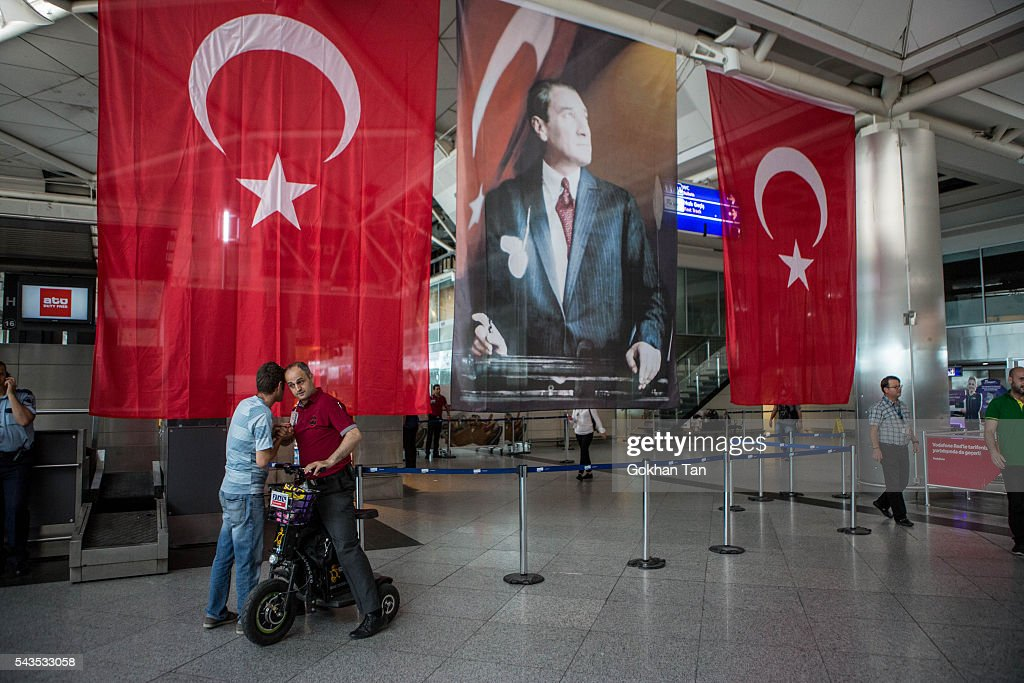 Men greet each other in front of Turkish flag and picture of modern Turkey's founder Mustafa Kemal Ataturk at Istanbul Ataturk airport on June 29, 2016 in Istanbul, Turkey. Three suicide bombers opened fire before blowing themselves up at the entrance to the main international airport in Istanbul yesterday. The Istanbul Governor's Office says 41 people have been killed, 37 of the victims have been identified, including 10 foreign nationals and three people with dual citizenship. More than 230 people were wounded but 109 have been discharged from hospitals in the deadly suicide bombing attack in Istanbul's Ataturk airport blamed on the Islamic State group.
