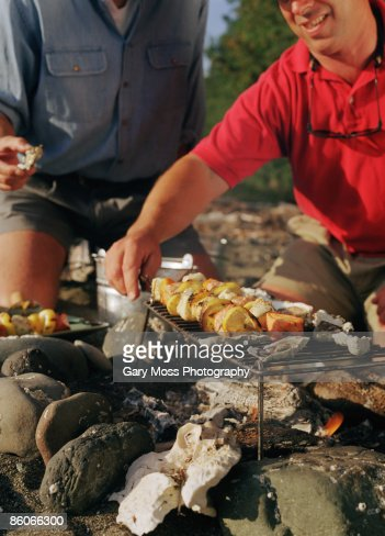 Men grilling seafood brochettes outdoors