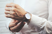 Businessman checking time on his wristwatch men  hand with a watch