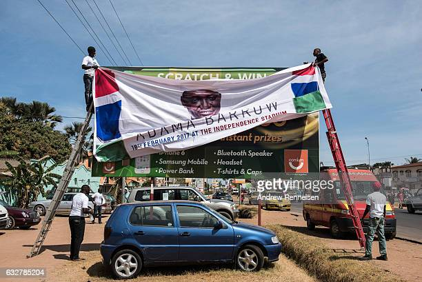 Men hang a banner for the inauguration ceremony of Gambian President Adama Barrow prior to his return on January 26 2017 in Banjul The Gambia Barrow...