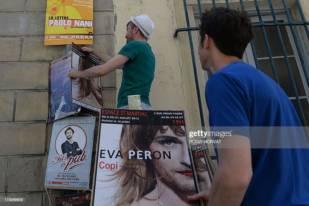 Men hang posters of various theater shows on July 6, 2013 next to Palais des Papes in Avignon, southeastern France, during the 67th International Theatre festival.