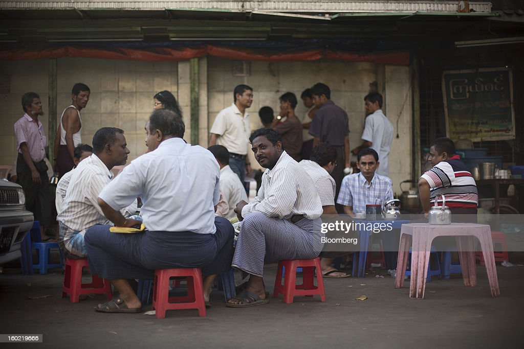 Men have tea at a roadside tea store in Yangon, Myanmar, on Tuesday, Jan. 22, 2013. Myanmar cleared about $1 billion in overdue debt with the Asian Development Bank and World Bank using a bridge loan from Japan, opening the door for increased lending as the country seeks to overhaul its infrastructure. Photographer: Brent Lewin/Bloomberg via Getty Images