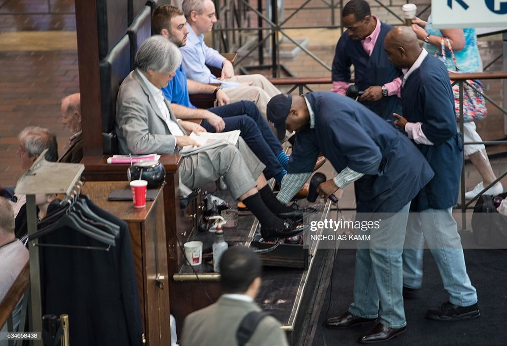Men have their shoes shined at Union Station in Washington, DC, on May 27, 2016. / AFP / Nicholas Kamm