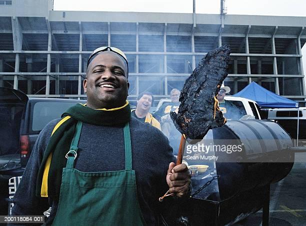 Men having tailgate party, man holding burned out steak