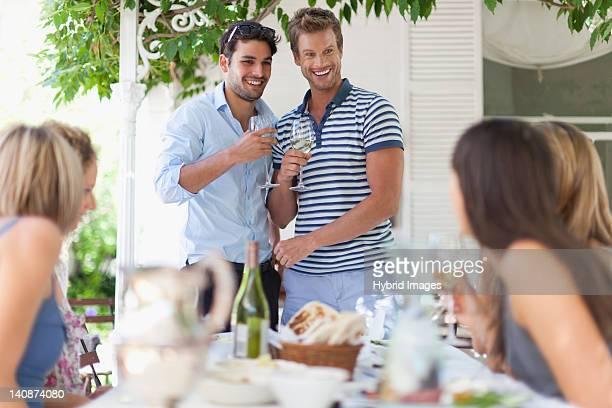 Hommes ayant vin à table en plein air
