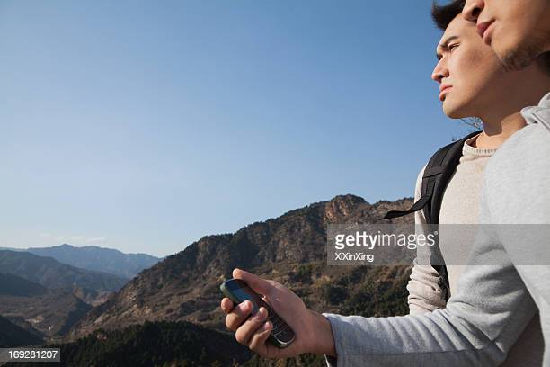 Men hiking and using GPS