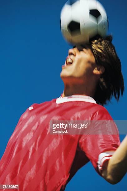 Men hitting soccer ball with head