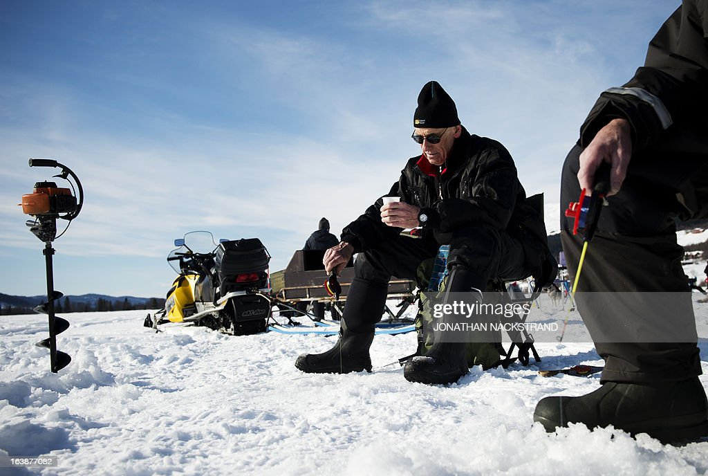 Men hold a fishing pole as they participate in an ice fishing contest on the frozen Oster-Jansjon lake in Are, Sweden on March 17, 2013.