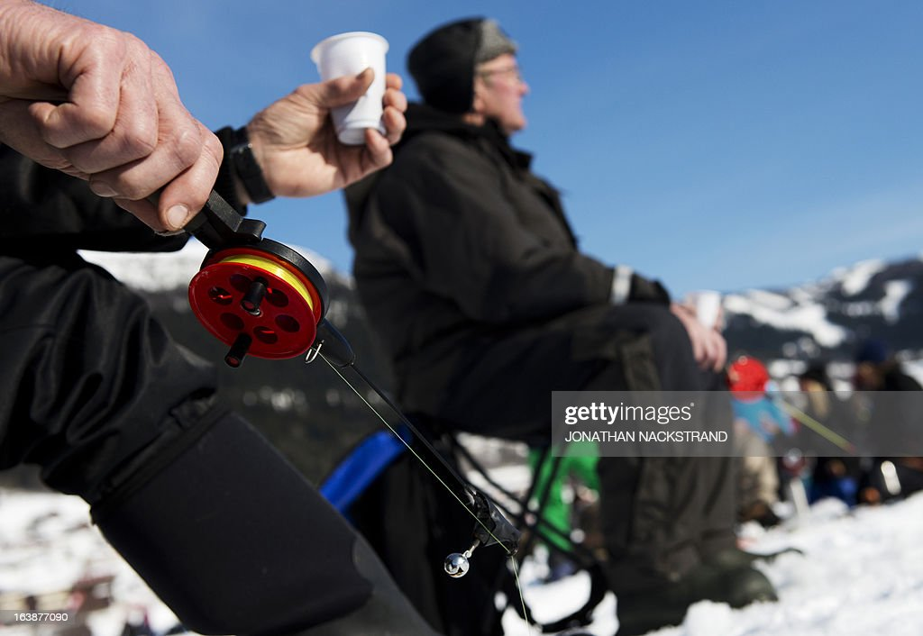 Men hold a fishing pole as they participate in an ice fishing contest on the frozen Oster-Jansjon lake in Are, Sweden on March 17, 2013. AFP PHOTO/JONATHAN NACKSTRAND
