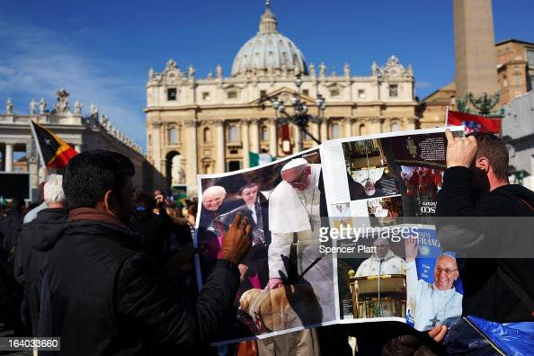 Men hold up a poster during the Inauguration Mass for Pope Francis in St Peter's Square on March 19 2013 in Vatican City Vatican The mass is being...