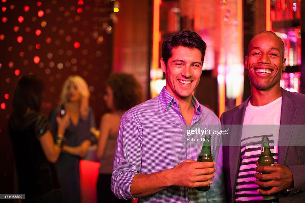 Men holding beer bottles in nightclub : Stock Photo
