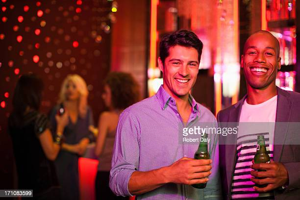 Men holding beer bottles in nightclub