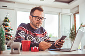 Men wearing blue sweater and eyeglasses holding credit card and using laptop at home office during christmas holidays
