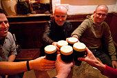 Men holding glasses of stout