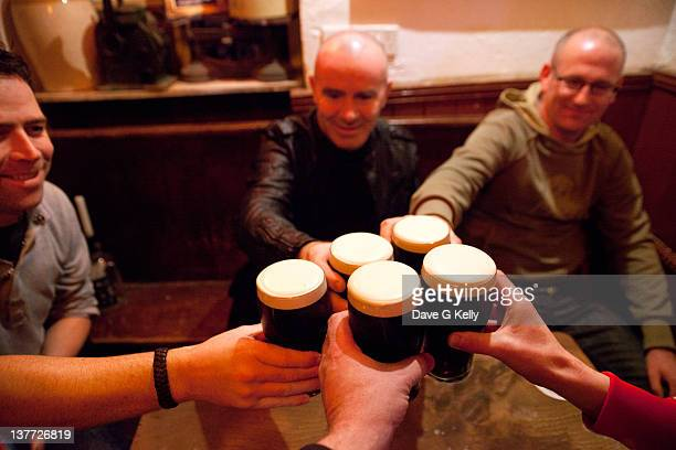 Men holding glasses of stout