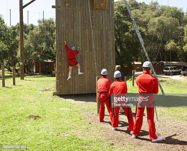 Men holding harness rope while colleague climbs obstacle wall