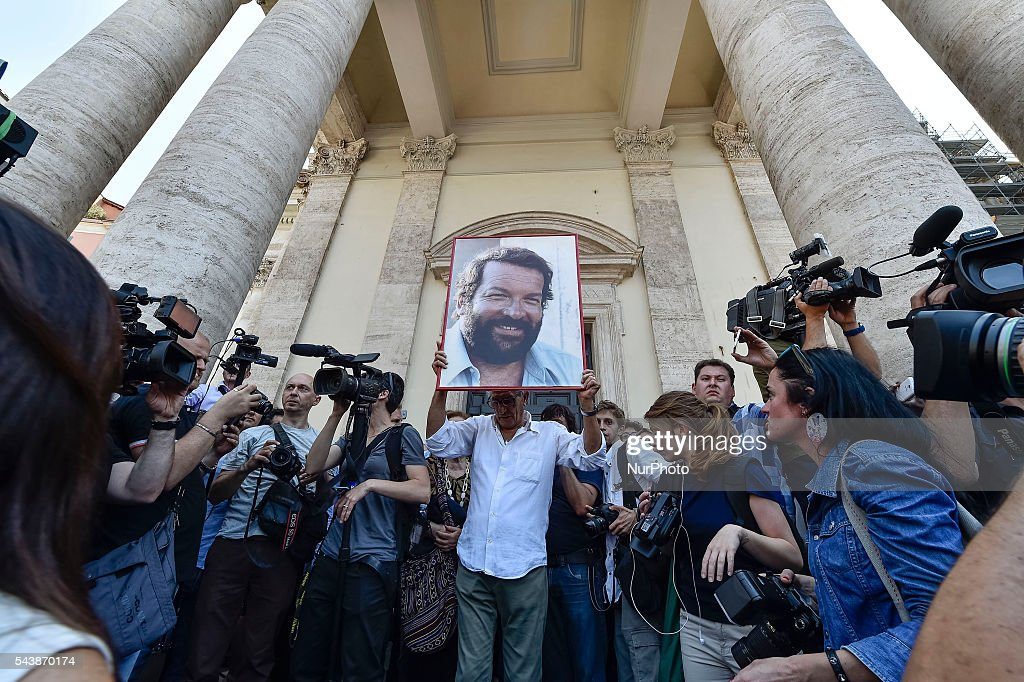 A men holds a portrait of Italian actor <a gi-track='captionPersonalityLinkClicked' href=/galleries/search?phrase=Bud+Spencer&family=editorial&specificpeople=707220 ng-click='$event.stopPropagation()'>Bud Spencer</a>, born Carlo Pedersoli, outside the church of the artists, Santa Maria in Montesanto, on June 30, 2016 at the end of the funeral of the actor at Piazza del Popolo in Rome