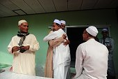Men hug each other following morning prayers at a mosque on the first day of Eid alFitr celebrations in Thailand's southern province of Narathiwat on...