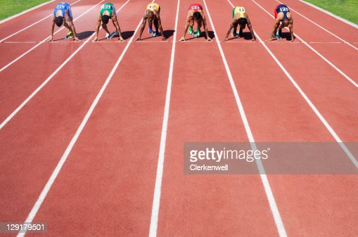 Men in a start block on an athletic track : Stock Photo