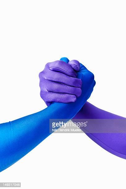 Men in bodysuits arm wrestling