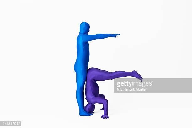 Men in bodysuits making the letter F