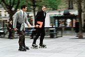 Men in business attire inline skating together along sidewalk carrying briefcase, folders under arm