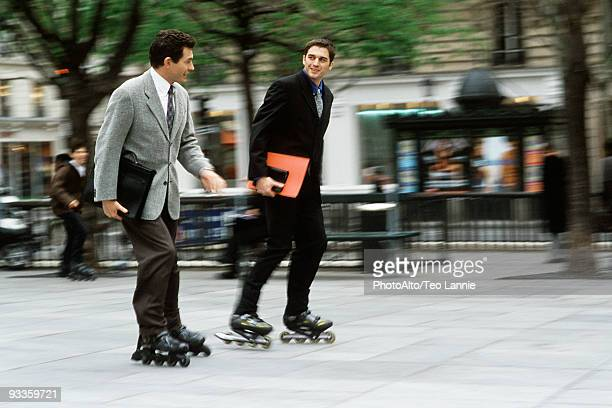 Men in business attire inline skating together along sidewalk carrying briefcase, folders under arm