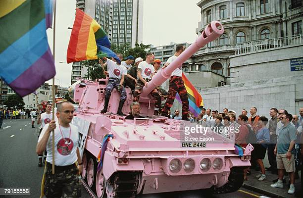 Men in camouflage trousers riding a pink tank and carrying rainbow flags during the Lesbian and Gay Pride event London 24th June 1995