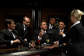 Men in dinner jackets drinking cocktails in bar, one holding cigar