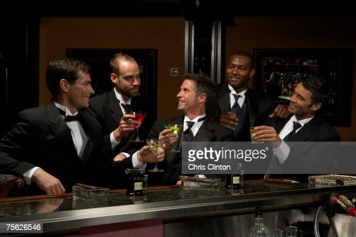 Men in dinner jackets drinking cocktails in bar : Stock Photo