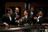 Men in dinner jackets drinking cocktails in bar