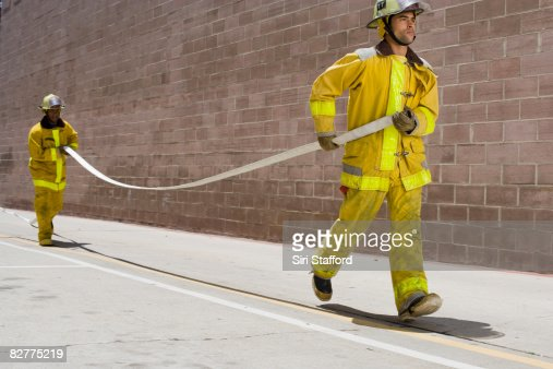 men in firefighter suits carrying hose : Stock Photo