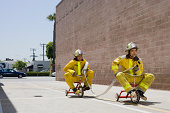 men in firefighter suits on tricycles
