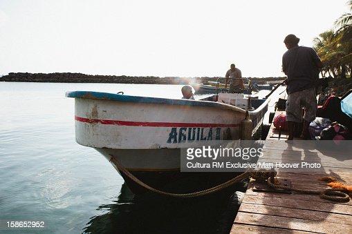 Men in fishing boat in water : Stock Photo
