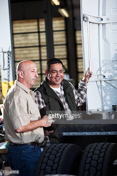 Hombres en el garaje con semi-truck