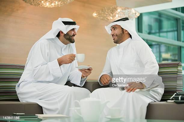 Men in kaffiyehs drinking coffee