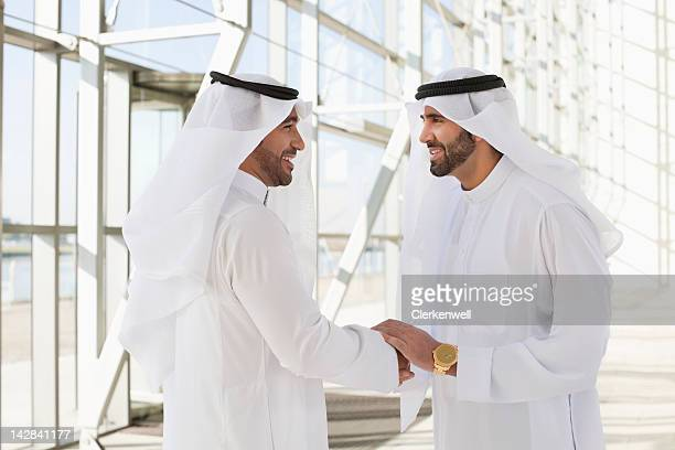 Men in kaffiyehs shaking hands