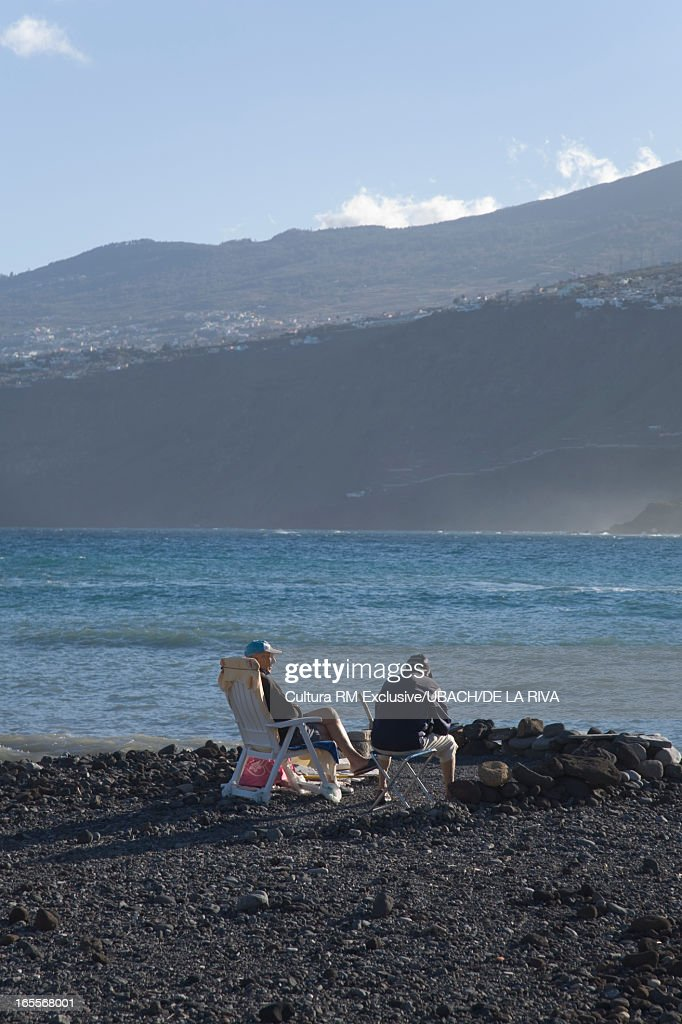 Men In Lawn Chairs On Rocky Beach : Stock Photo