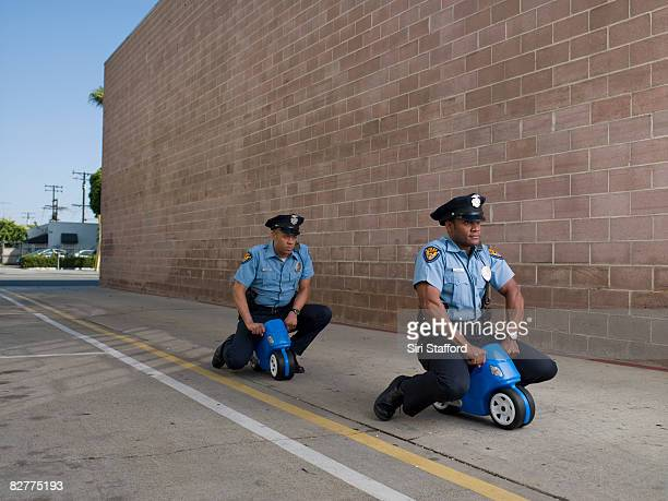 men in police uniforms riding toy motorcycles